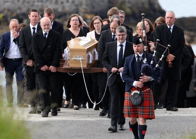 A lone piper playing in front of a coffin at a funeral