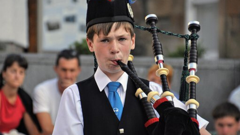 young boy learning to play the bagpipes