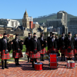 Nelson Mandela Artillery Pipes and drums surrounded by Cape Town city centre and Signal Hill