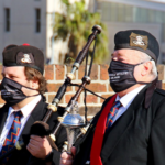 The Nelson Mandela Artillery drum major with one of the pipers wearing their branded masks