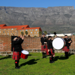 The bagpipers and drummers of Nelson Mandela Artillery playing while Table Mountain watches on